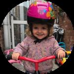 Toddler on a bike wearing pink helmet