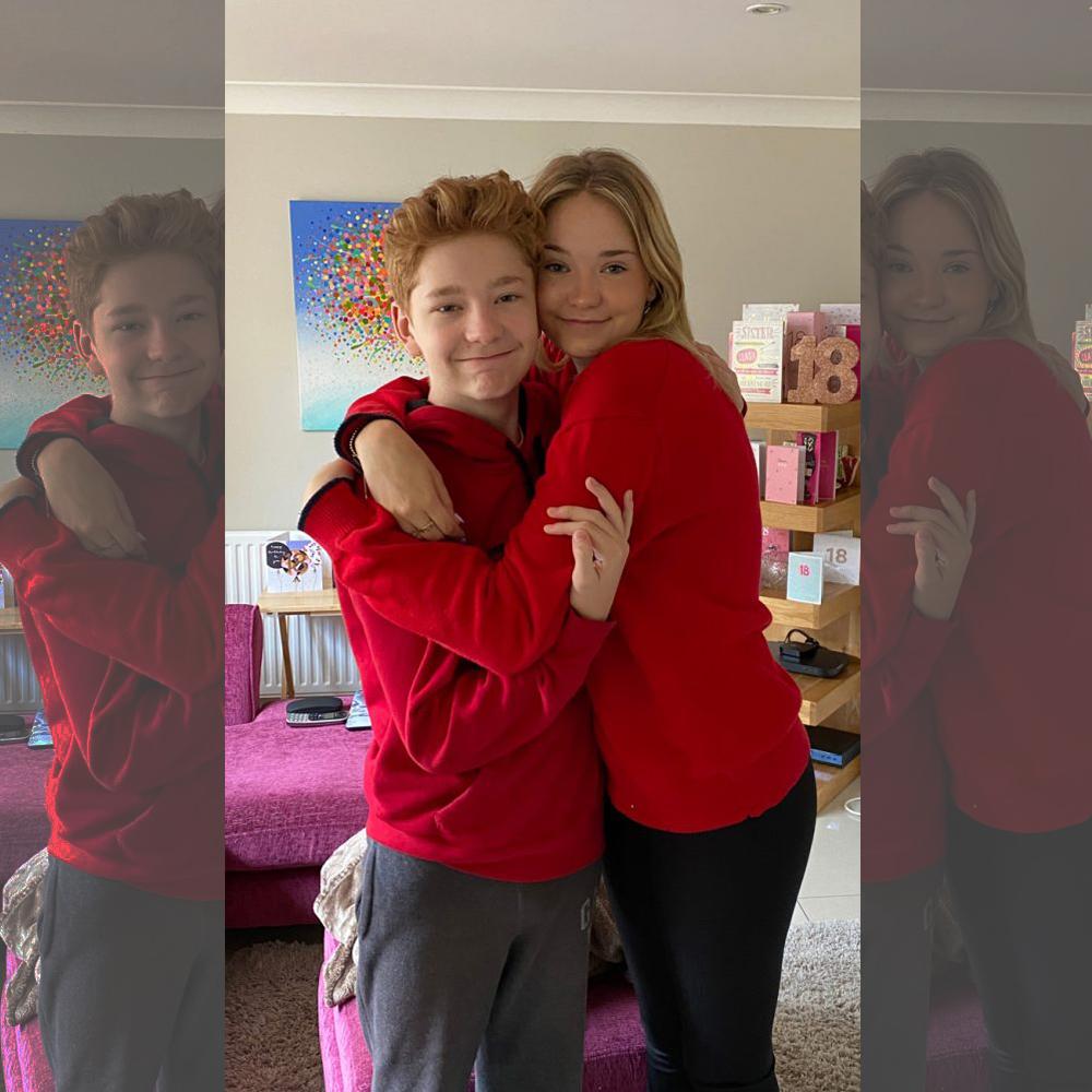 Siblings wearing red, hugging
